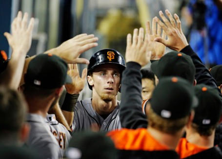 San Francisco Giants' Matt Duffy celebrates after scoring in the dugout on a double by Marlon Byrd during the eighth inning of a baseball game against the Los Angeles Dodgers in Los Angeles, Monday, Aug. 31, 2015. (AP Photo/Chris Carlson)